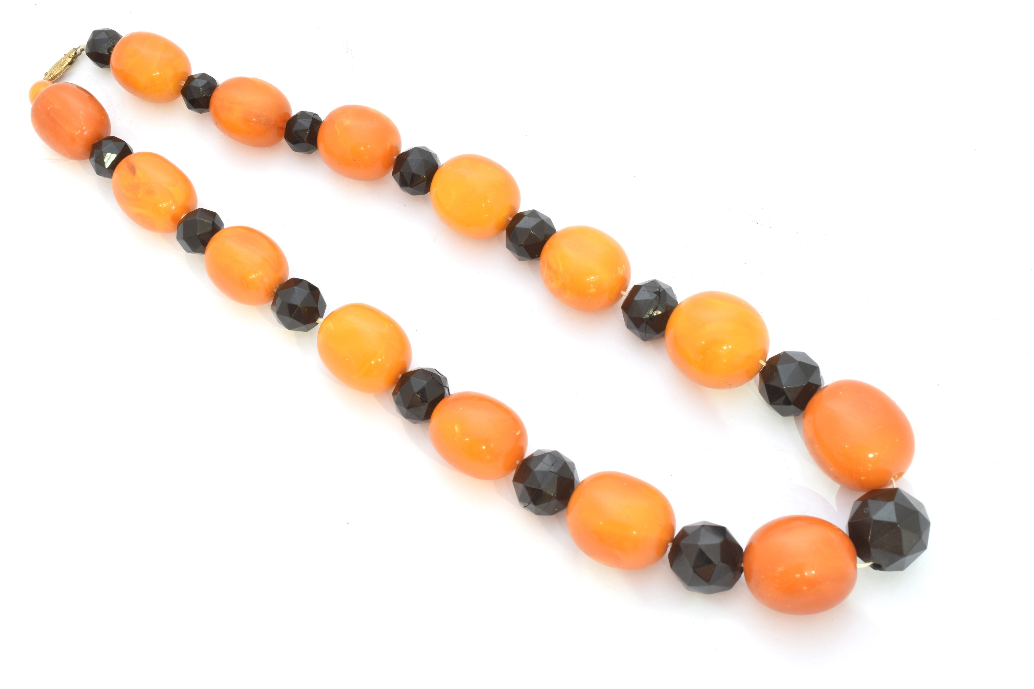 A butterscotch amber and jet necklace, designed as a series of graduated faceted jet and oval butterscotch amber beads, length 61.5cm, gross weight 134g.