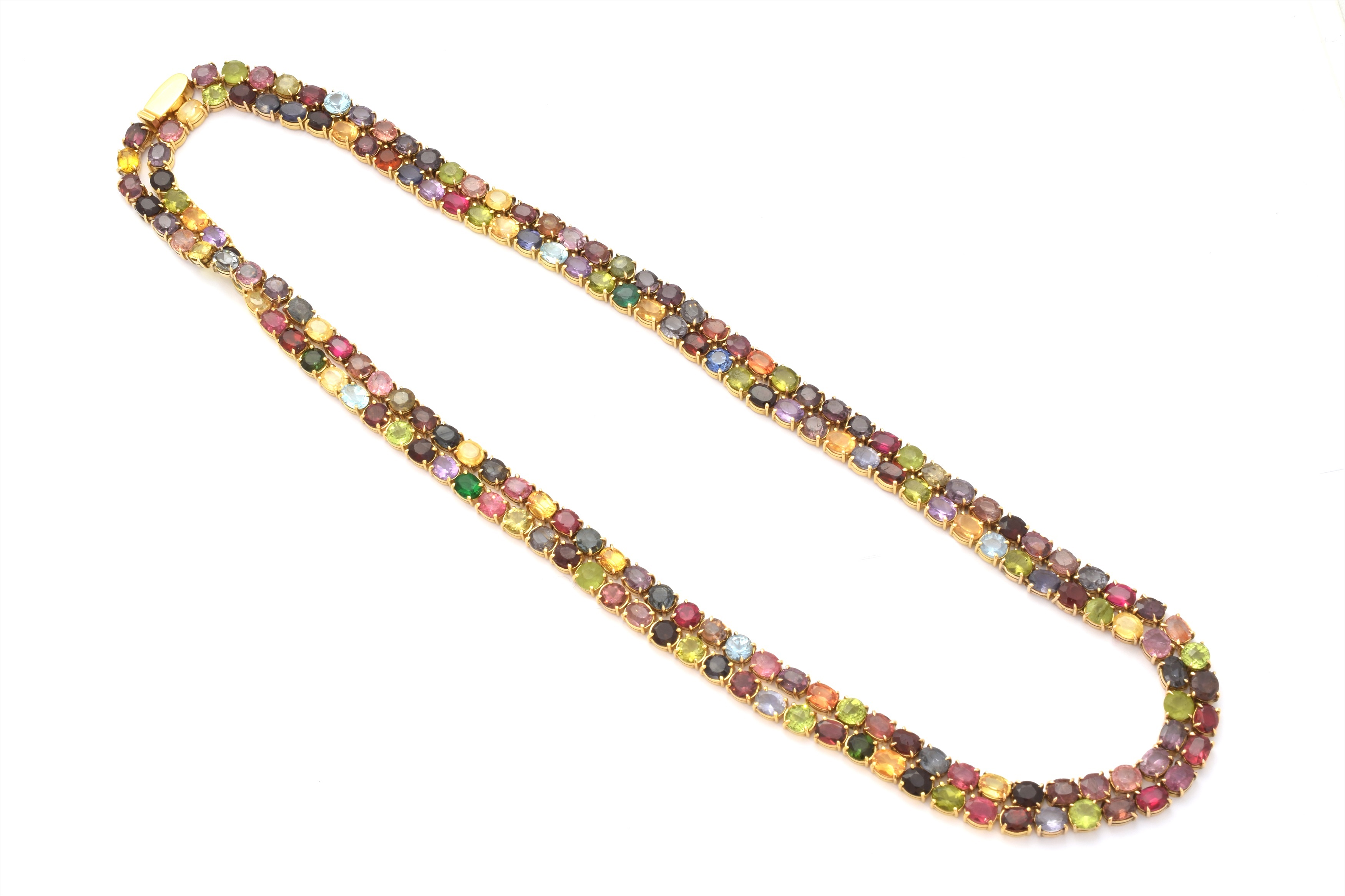 A multi gem rivière necklace, designed as an oval and circular shape vari gem line, including ruby, peridot, spinel, garnets, amethyst, iolite, citrine, sapphire, topaz and other gemstones, with a polished push-piece clasp, stamped 750, length 116cm, gross weight 92.4g.