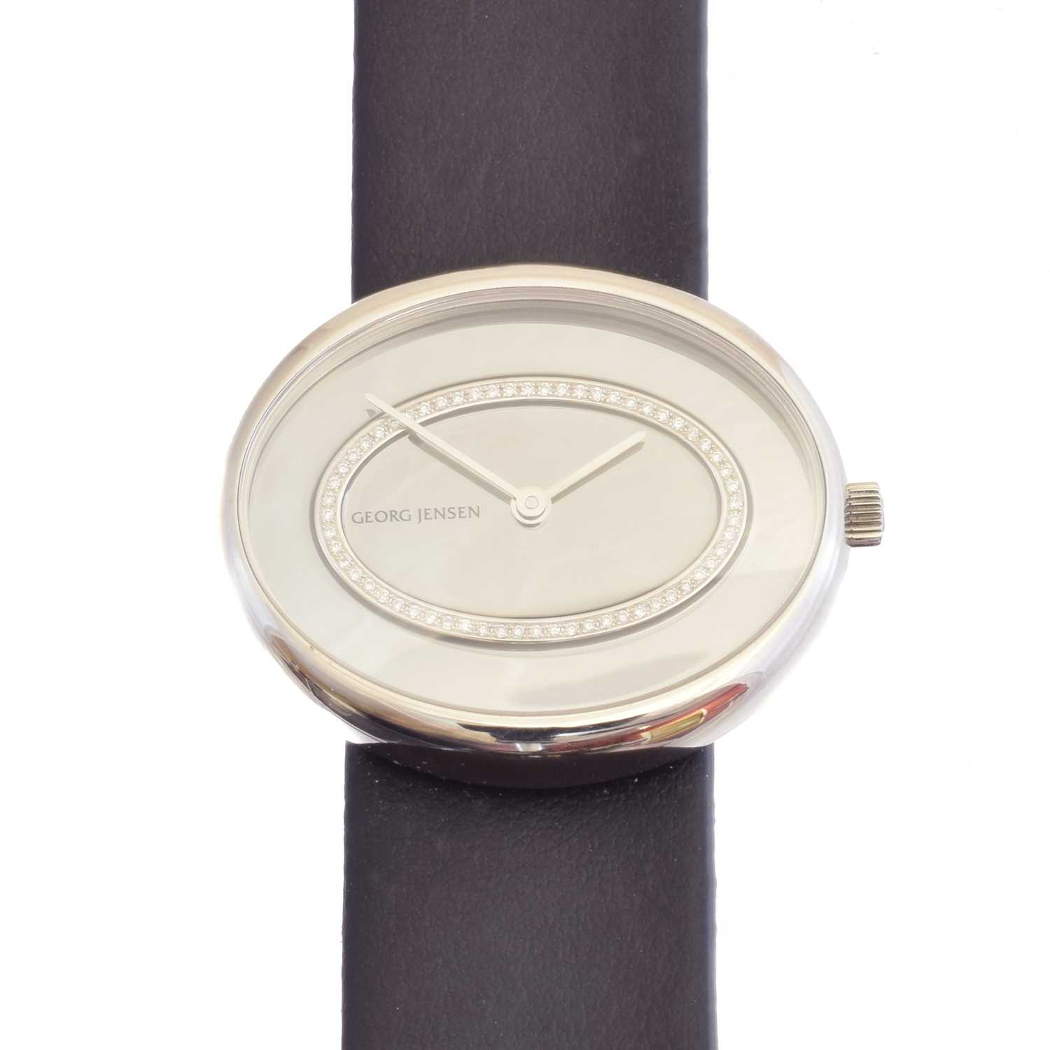 A Georg Jensen Vivianna Oval watch, model no. 323, the oval signed mirrored dial with brilliant cut diamond halo detailing, within a stainless steel case, reference no. 003632, total diamond weight 0.13ct, case diameter 34mm. With two leather straps, box and paperwork.
