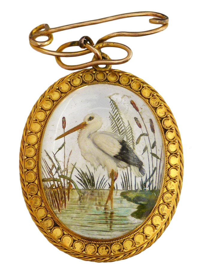 A late Victorian Essex Crystal pendant, the oval reverse carved intaglio depicting a stork wading amongst bullrushes, within a cannetille border and with brooch surmount, length 5cm.