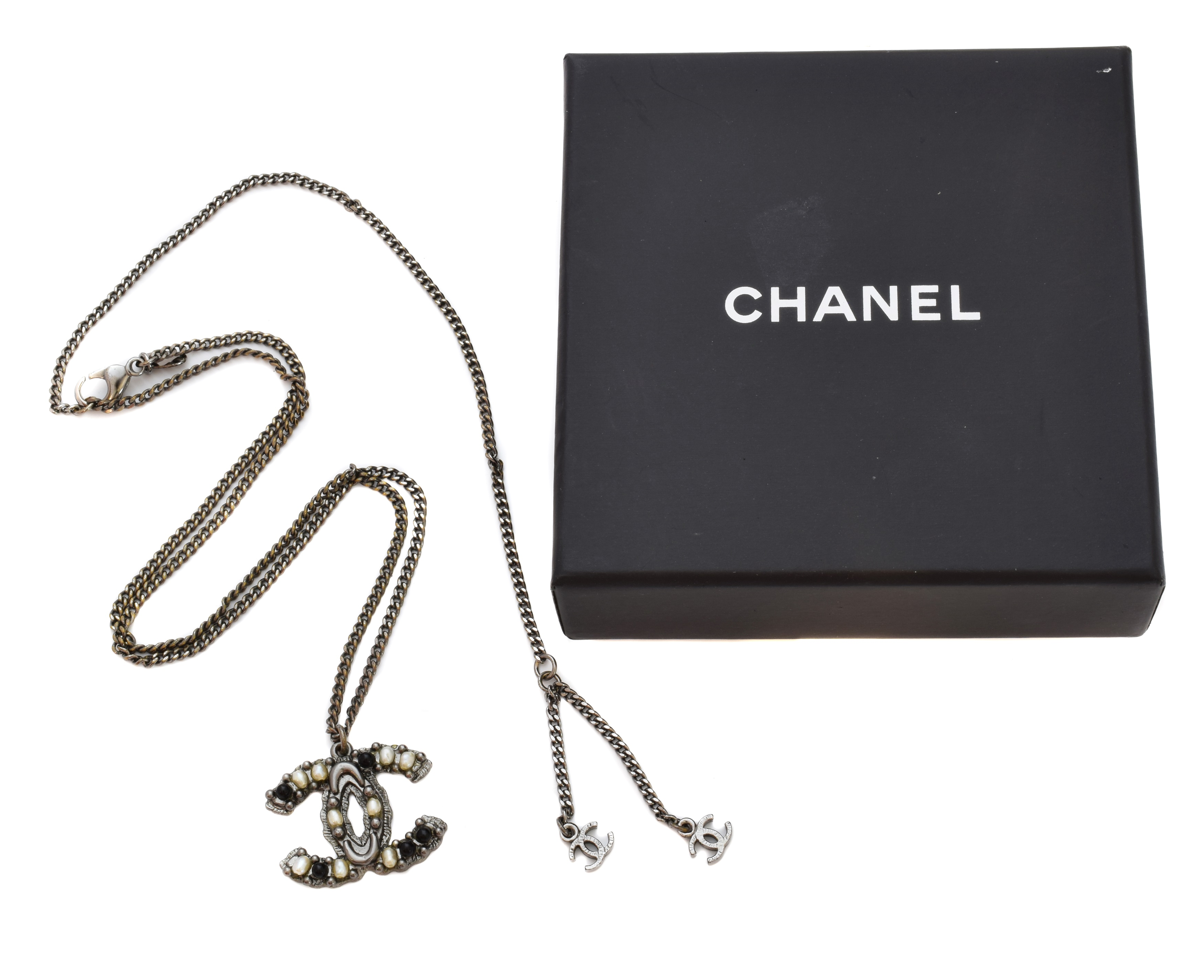 A Chanel necklace, the imitation pearl and black paste CC suspended from a flat curb link chain, signed and numbered Chanel A11, length of pendant 2.3cm, length of chain 42cm. With maker's pouch and box.