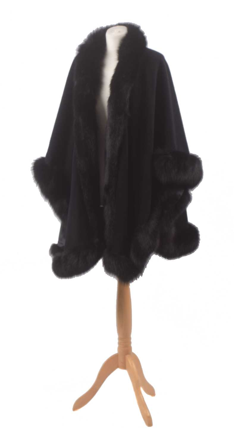 A fur tipped wool cape, the black wool cape with undulating hem and black fur trim.