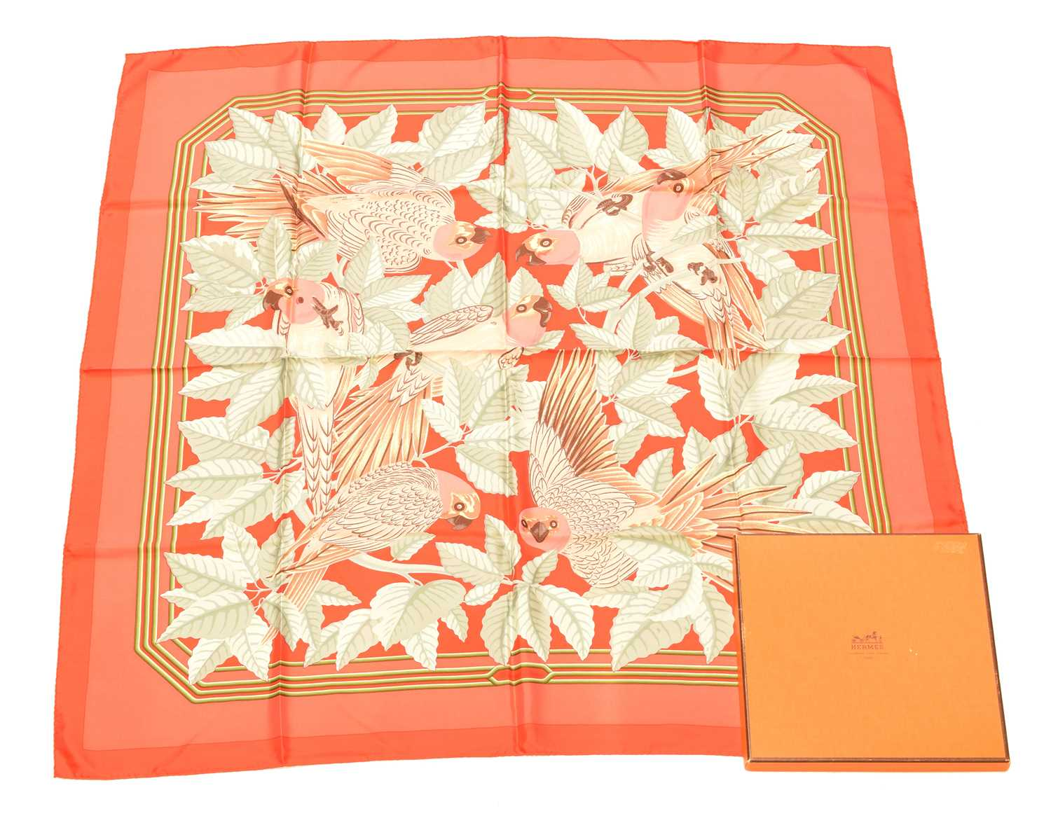 "A Hermès ""Les Perroquets"" silk scarf by Joachim Metz, the pink, red, green and brown pattern depicting parrots, signed Hermès. With maker's box."