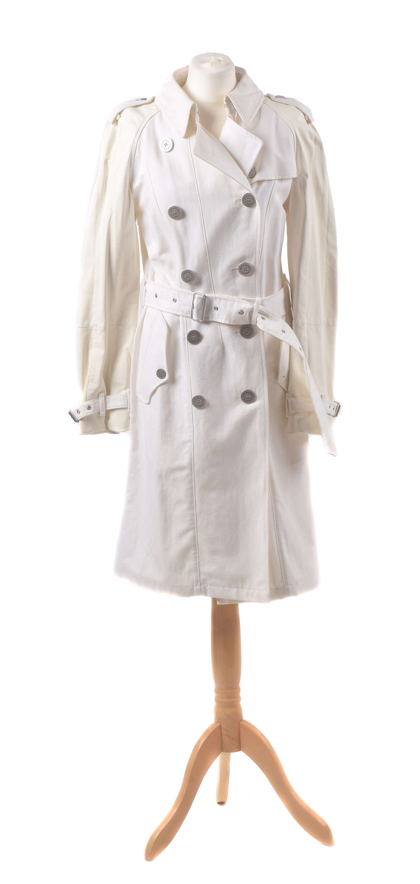 A Burberry trench coat, the cream canvas trench coat with cream leather sleeves and oversized silver tone buttons bearing maker's name, size 10.