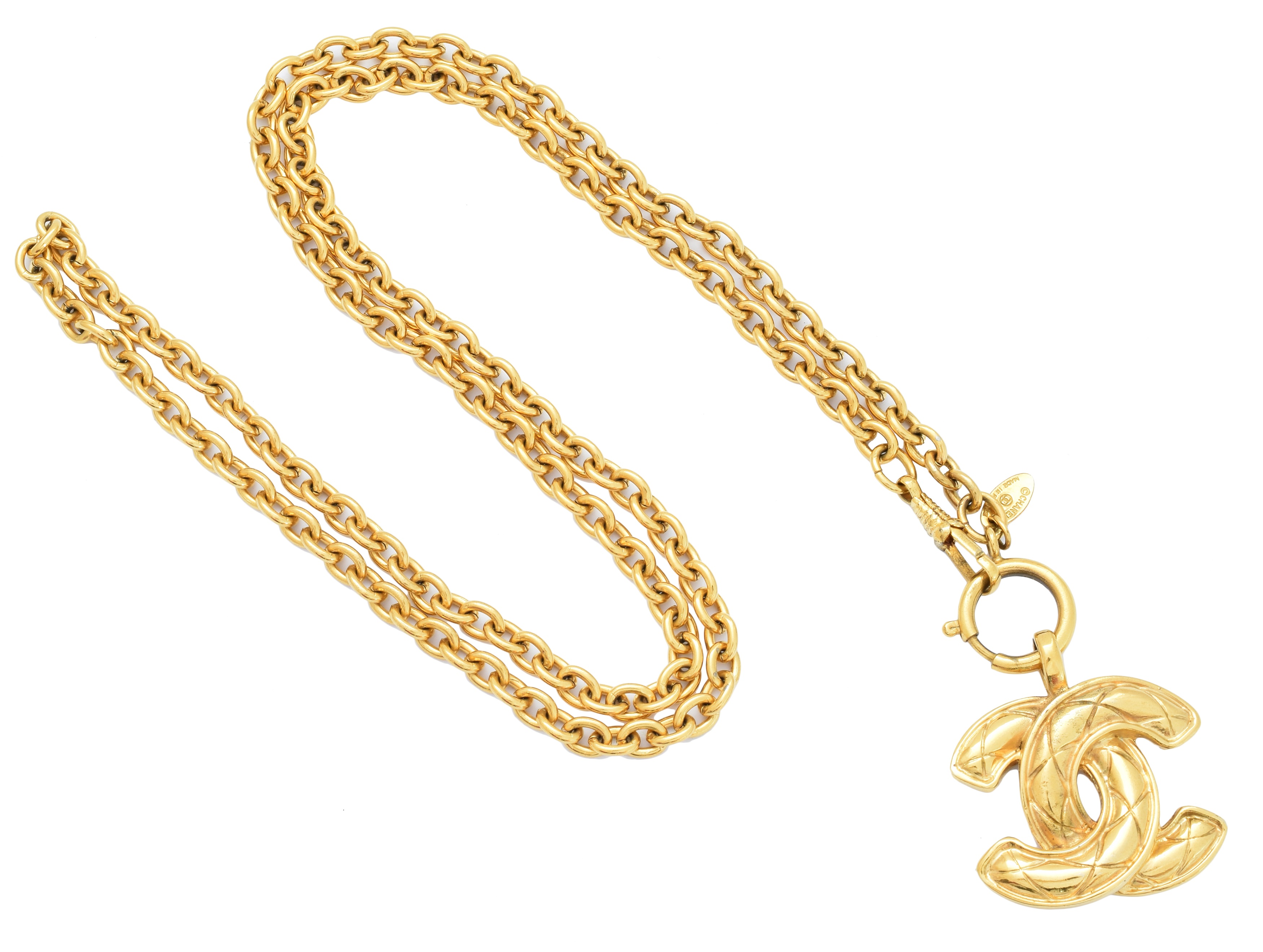 A Chanel pendant necklace, the gold-tone maker's quilted monogram suspended from a trace link chain, signed Chanel.