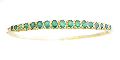 Lot 13 - An 18ct gold emerald hinged bangle